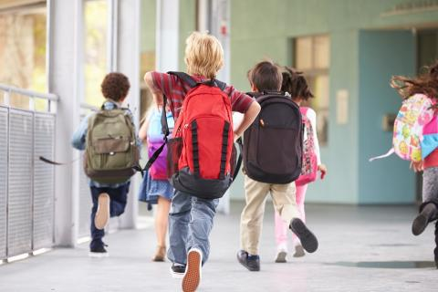 Elementary students running through school hall with backpacks
